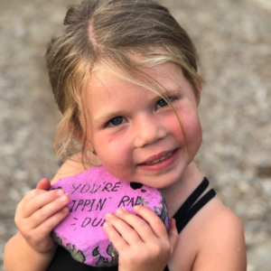 Little girl holding a painted rock